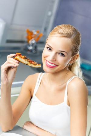Young happy woman with pizza, indoors Stock Photo - 9751094