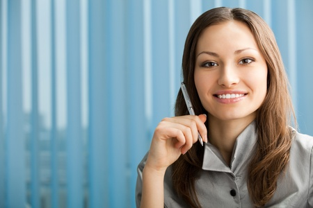 Portrait of beautiful young happy smiling businesswoman with pen at office photo