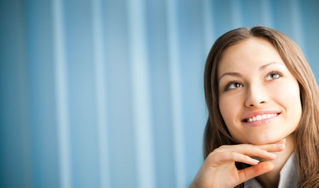 think big: Portrait of thinking smiling business woman at office.