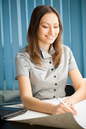 Portrait of writing happy smiling businesswoman working at office photo