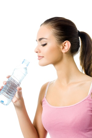 Young happy smiling woman in sportswear with water, isolated on white background photo
