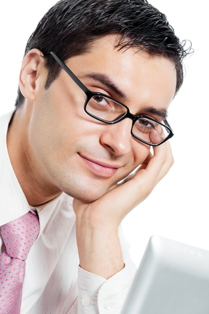 Portrait of young happy smiling businessman in glasses working with laptop, isolated on white background photo