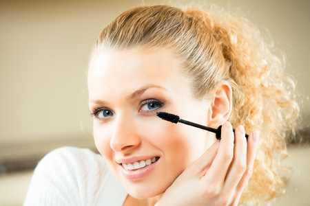 Young woman applying mascara with lash brush at home photo