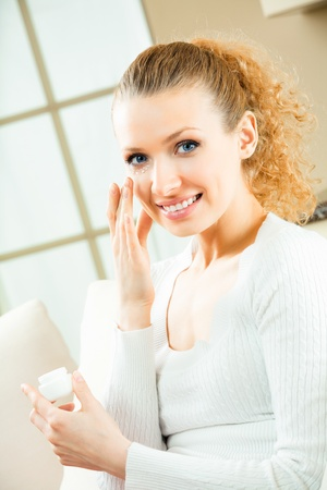 humidify: Young beautiful happy smiling woman applying moisturiser creme, at home Stock Photo