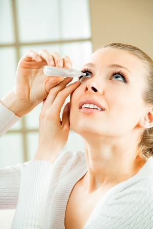 Photo of young woman dripping eye with eyes drops at home Фото со стока