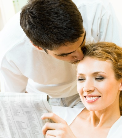 Young happy amorous couple reading newspaper at home photo