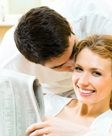 Young happy amorous couple reading newspaper at home Stock Photo - 9896081