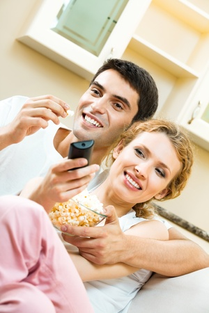 Young couple eating popcorn and watching TV together at home photo