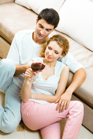 Young happy amorous couple celebrating with redwine at home photo