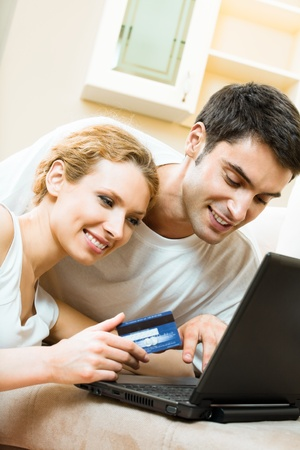 Young happy smiling couple with laptop, paying by credit card in internet store, at home Stock Photo - 9896092