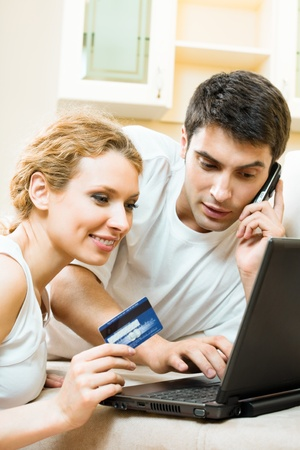 Young happy smiling couple with laptop, paying by credit card in internet store, at home Stock Photo - 9896088