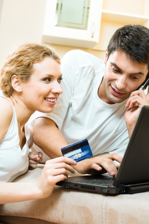 Young happy smiling couple with laptop, paying by credit card in internet store, at home Stock Photo - 9896090