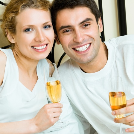 Young happy smiling amorous couple celebrating with champagne at bedroom photo