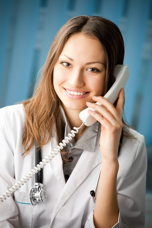 Portrait of happy smiling cheerful young female doctor on phone at office photo