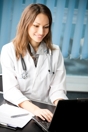 Happy smiling female doctor or nurse working with laptop at office photo