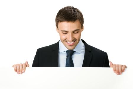 letreros: Feliz hombre de negocios joven sonriente que muestra se�al en blanco, aislado en fondo blanco Foto de archivo