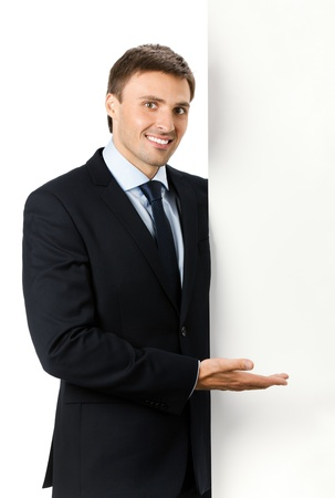 Happy smiling young business man showing blank signboard, isolated on white background Stock Photo - 9896368