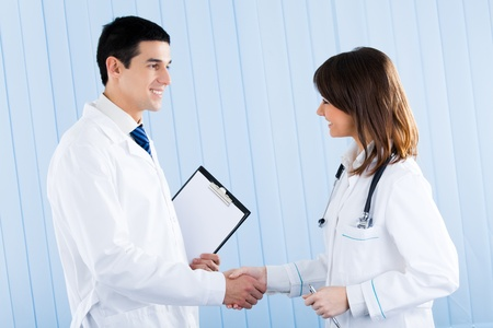 handshaking: Two medical people handshaking at office