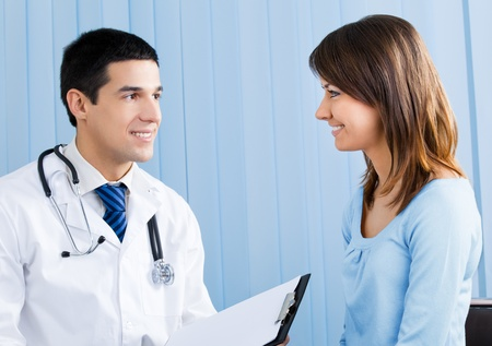 Young doctor and female patient with prescription at office photo