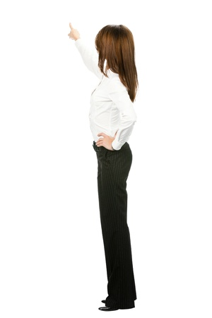 Full body of young business woman pointing at something in her back, isolated on white background photo