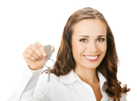 whitebackground: Young happy smiling business woman or real estate agent showing keys from new house, isolated on white background. Focus on keys.