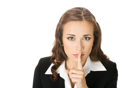 seriously: Portrait of young serious business woman keeping finger on her lips and asking to keep quiet, isolated on white background