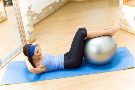 home gym: Young happy smiling woman doing fitness exercises with fit ball at home