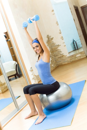 Young happy smiling woman doing fitness exercises with fit ball and dumbbells at home photo