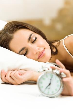 woman clock: Retrato de joven bella mujer con reloj despertador acostado en la cama, en casa