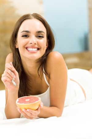 portarit: Portarit of young happy smiling beautiful woman eating grapefruit on bed, at home Stock Photo