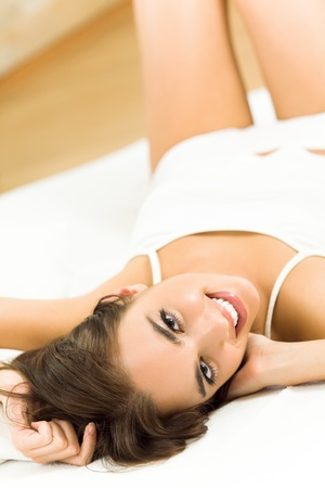 Portrait of young happy smiling beautiful woman waking up at home photo