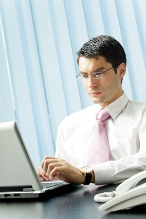 seriously: Businessman with laptop at office