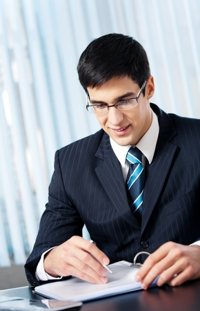 businessman signing documents: Portrait of writing smiling businessman working at office Stock Photo
