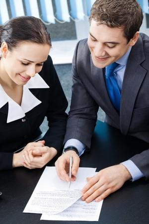 n�gociation: Deux jeunes hommes d'affaires sourire heureux, ou homme d'affaires et clients de travailler avec des documents au bureau