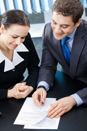 Two young happy smiling businesspeople, or businessman and client working with documents at office photo