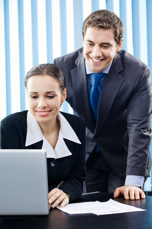 Two happy smiling young businesspeople working with laptop at office photo