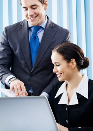 net meeting: Two happy smiling young businesspeople working with laptop at office Stock Photo