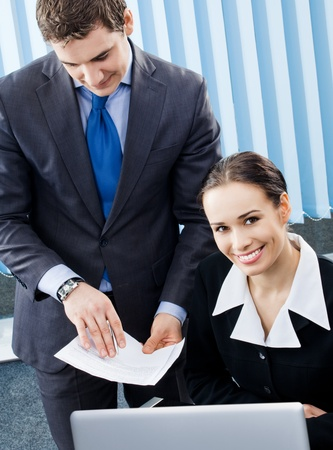 Two happy smiling young businesspeople working with laptop and documents, at office photo