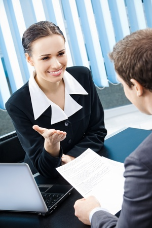 happy client: Two young happy smiling businesspeople, or business woman and client working with documents at office Stock Photo