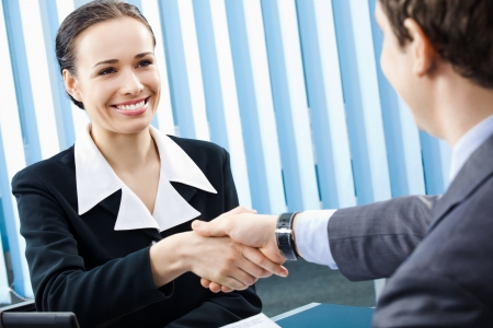 Two happy businesspeople or business woman and client handshaking at office