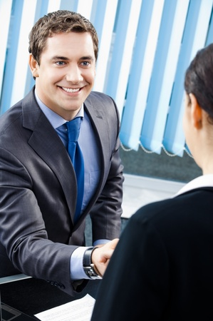 Two happy businesspeople or businessman and client handshaking at office photo