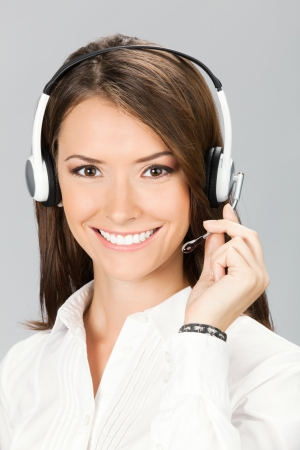 handsfree phone: Portrait of happy smiling cheerful customer support phone operator in headset, over grey background