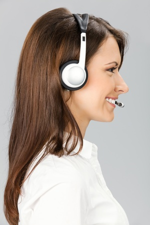 profile view: Portrait of happy smiling cheerful customer support phone operator in headset, over grey background