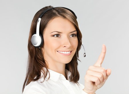 Portrait of happy smiling cheerful customer support phone operator in headset pointing at something, over grey background Stock Photo - 10468176