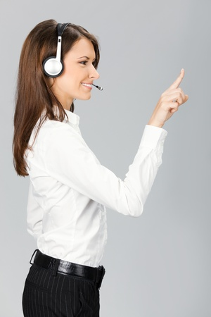 Portrait of happy smiling cheerful customer support phone operator in headset pointing at something, over grey background Stock Photo - 10468137