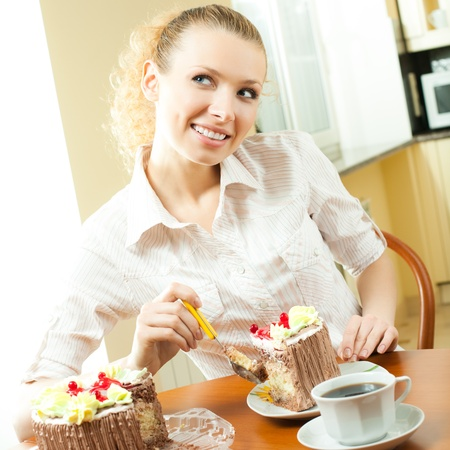Young happy smiling beautiful woman eating torte at home Stock Photo - 10467988