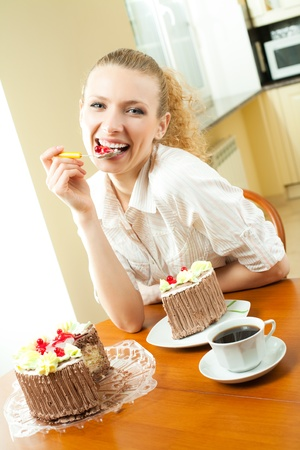 torte: Young happy smiling beautiful young woman eating torte at home