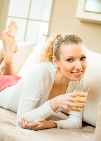Young happy smiling woman drinking orange juice at home photo