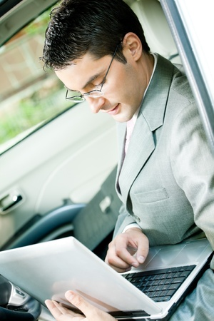 Young businessman working with laptop in the car photo