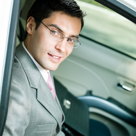 Portrait of young happy smiling businessman in the car photo
